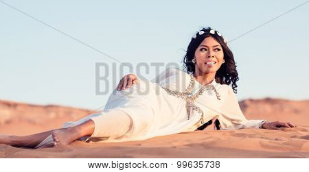 Woman laying in sand of Arabian desert