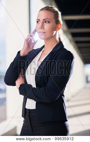 Business woman with phone outdoors standing in front of building