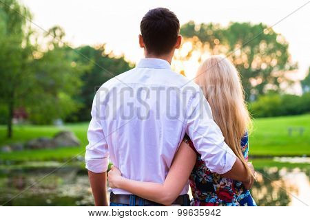 Couple dreaming their life together looking in romantic sunset, man embracing his girlfriend