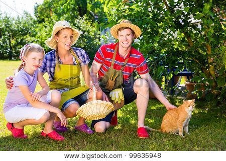 Family with cat gardening in garden