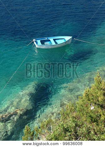 BISEVO, CROATIA - 21 AUGUST 2015: Little wooden fishing boat moored in bay on the island of Bisevo.