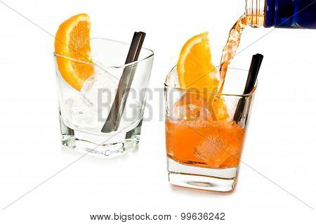 Barman Pouring Spritz Aperitif Aperol Cocktail In Two Glasses With Orange Slices And Ice Cubes