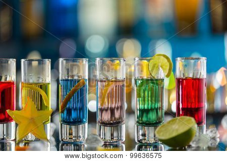 Variation of hard alcoholic shots served on bar counter. Blur bottles on background