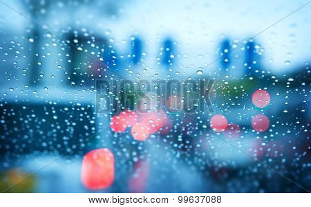 Rainy day traffic abstract. Traffic seen from  inside a car. Rain drops on windshield and car tail lights in bokeh.