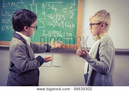 Pupils dressed up as teachers discussing in a classroom in school