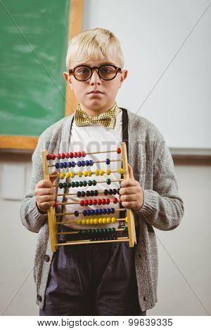 Portrait of pupil dressed up as teacher holding abacus in a classroom