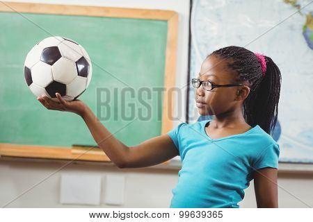 Cute pupil holding football in a classroom in school
