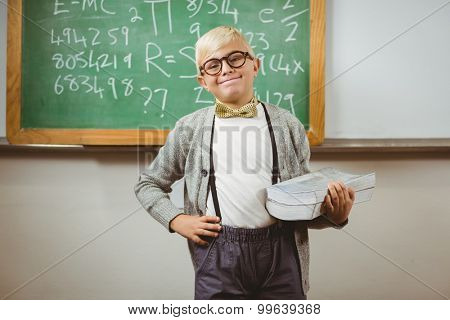 Portrait of smiling pupil dressed up as teacher holding books in a classroom