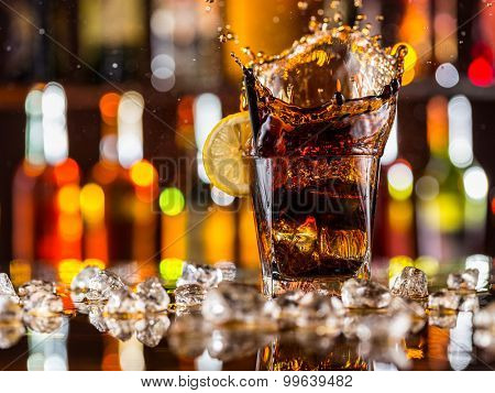 Glass of cola splashing out, placed on bar counter