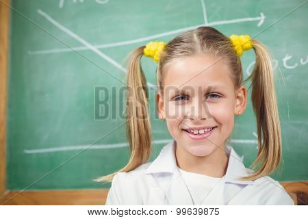 Portrait of cute pupil with lab coat in front of chalkboard in a classroom