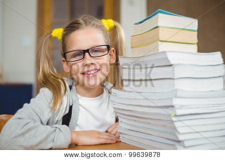 Portrait of smiling pupil next to stack of books on her desk in a classroom