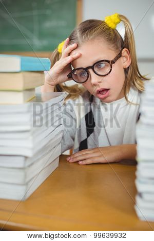 Overwhelmed pupil between stack of books on her desk in a classroom