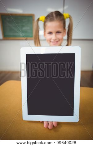 Smiling pupil showing tablet to camera in a classroom in school