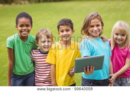 Portrait of smiling classmates holding tablet on campus