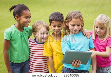 Smiling classmates looking at tablet on campus