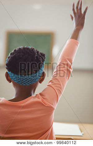 Rear view of pupil raising hand in a classroom in school