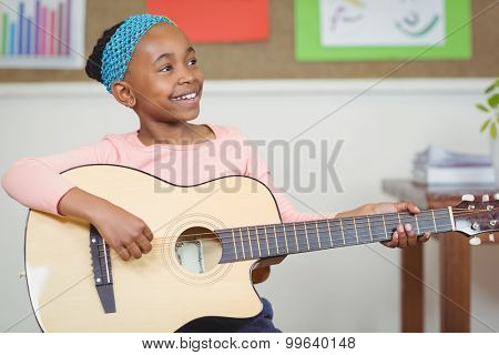 Smiling pupil playing guitar in a classroom in school