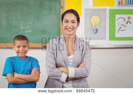 Portrait of pretty teacher and cute pupil in front of chalkboard in a classroom