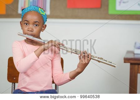 Portrait of cute pupil playing flute in a classroom in school