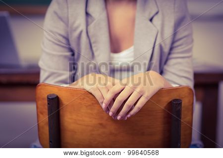 Teacher sitting on chair in a classroom in school
