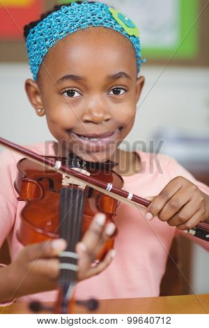 Portrait of smiling pupil playing violin in a classroom in school