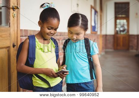 Cute pupils looking at smartphone at corridor in school