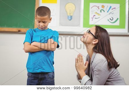 Pretty teacher begging pupil for something in a classroom