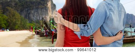 people, homosexuality, travel and gay love concept - close up of happy lesbian couple hugging over thailand beach background