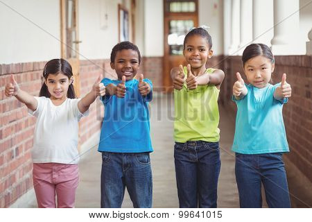 Portrait of cute pupils doing thumbs up at corridor in school