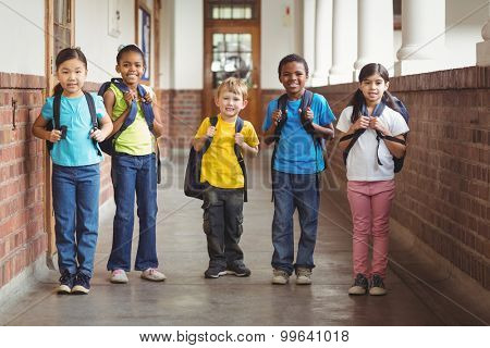 Portrait of cute pupils with schoolbags standing at corridor in school