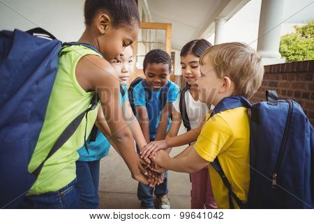Happy pupils putting hands together at corridor in school
