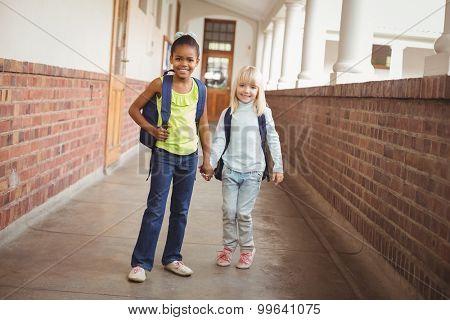 Portrait of smiling pupils holding hands at corridor in school