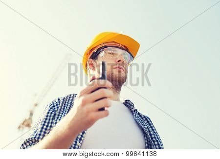 business, building, technology and people concept - builder in hardhat with radio outdoors