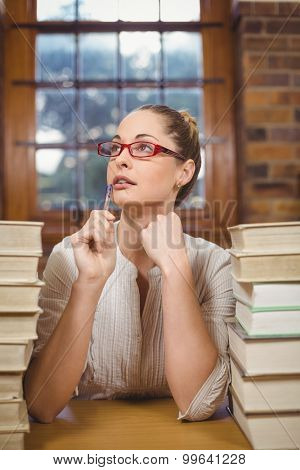 Thoughtful blonde teacher sitting between books in the library in school