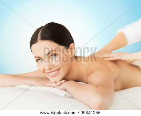 people, beauty, spa and body care concept - happy beautiful woman having back massage over blue background