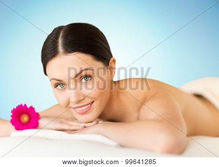 people, beauty, spa and body care concept - happy beautiful woman lying on massage desk at spa over blue background
