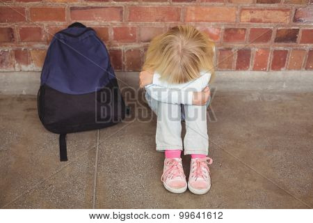 Sad pupil sitting alone on ground at corridor