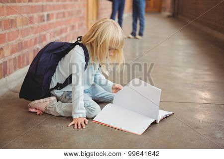 Cute pupil kneeling over notepad at corridor in school