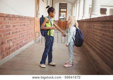 Smiling pupils holding hands at corridor in school