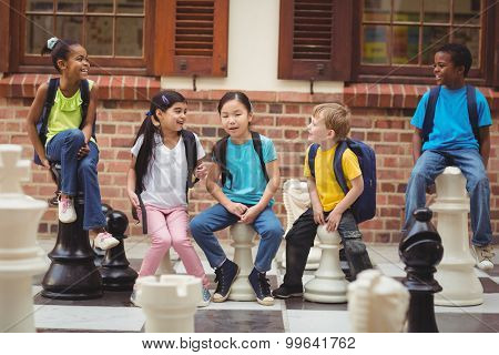 Happy pupils sitting on giant chess pieces in school