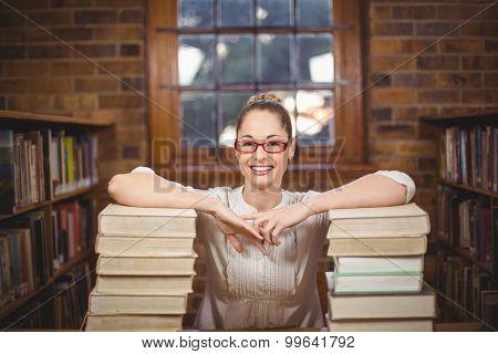 Portrait of blonde teacher standing between books in the library in school