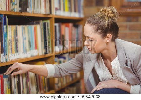 Blonde teacher searching book in the library in school