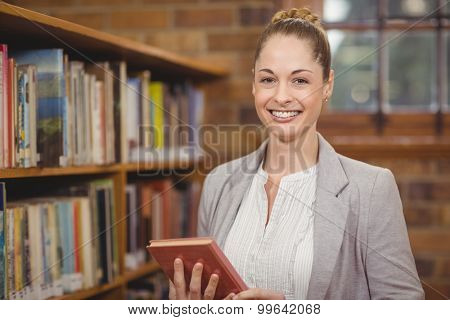 Portrait of blonde teacher holding book in the library in school