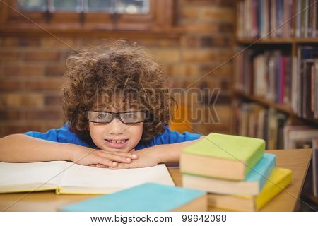 Portrait of cute pupil leaning on books in the library in school