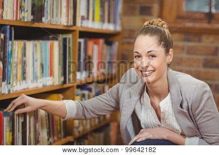 Portrait of blonde teacher searching book in the library in school