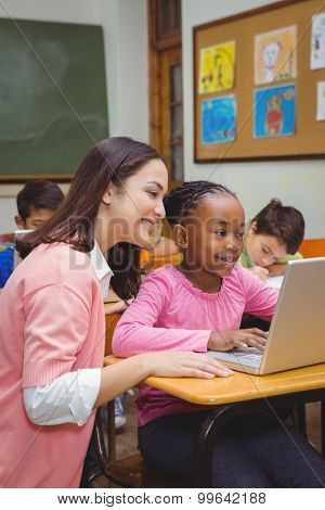 Happy teacher using laptop with student at the elementary school
