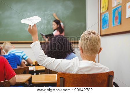 Student about to throw a paper airplane at the elementary school