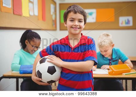 Smiling student holding a football at the elementary school