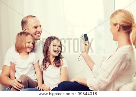 family, children, photography and home concept - smiling happy mother taking picture of father and two daughter at home
