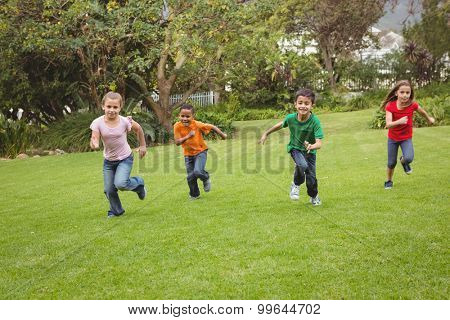 Happy kids running across the grass in a park area